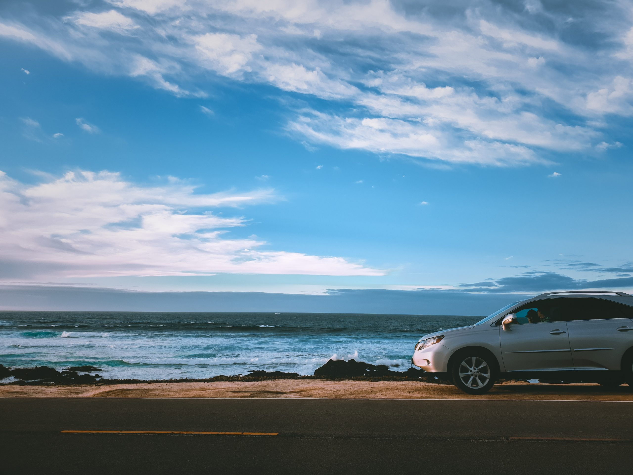 Car driving by the ocean